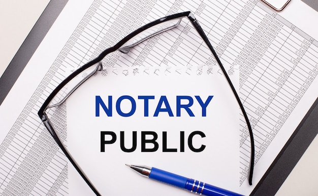 On a light background, a report, black-framed glasses, a pen and a sheet of paper with the text notary public. business concept