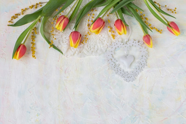 On a light background tulips, mimosa, lace and heart