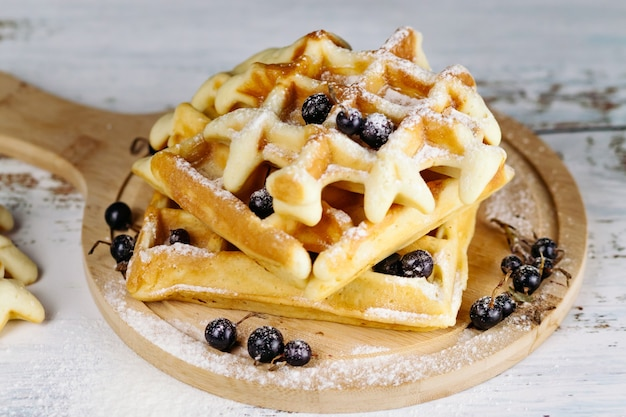 On a light background, viennese waffles are stacked on a round board, one on one. golden waffles are decorated with black currants.