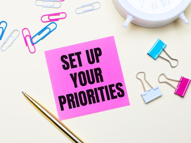 On a light background, a white alarm clock, pink, blue and white paper clips, a golden pen and a pink sticker with the text set up your priorities