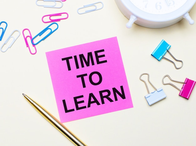 On a light background, a white alarm clock, pink, blue and white paper clips, a golden pen and a pink sticker with the text time to learn