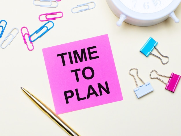 On a light background, a white alarm clock, pink, blue and white paper clips, a golden pen and a pink sticker with the text time to plan