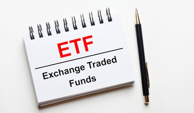 On a light background, a white notebook with are words etf exchange traded funds and a pen