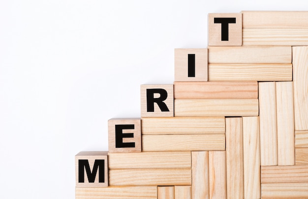 On a light background, wooden blocks and cubes with the text merit