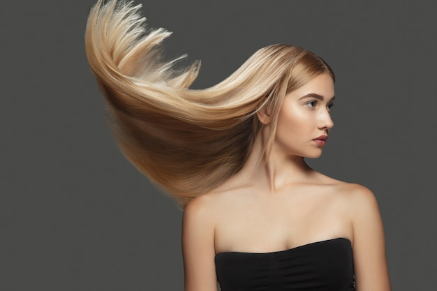Light beautiful model with long smooth flying blonde hair on dark grey studio background