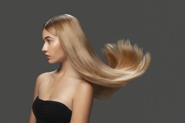 빛. 어두운 회색 스튜디오 배경에 길고 매끄럽고 날아다니는 금발 머리를 가진 아름다운 모델입니다. 잘 관리된 피부와 머리카락이 공중에 부는 젊은 백인 모델. 살롱 케어, 뷰티, 패션의 개념입니다.