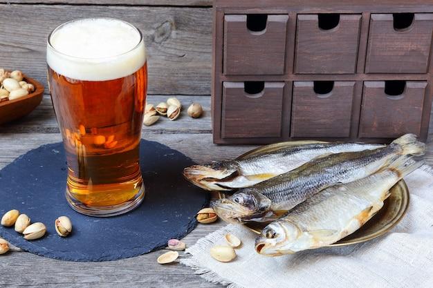 Светлое пиво и вяленая рыба - корюшка и вобла, традиционная русская закуска к пиву, на деревянном сером столе