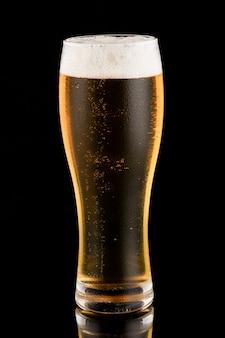 黒の背景にグラスで軽いビール