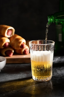 Light beer pours into a glass. sausages in the dough on the board in the background