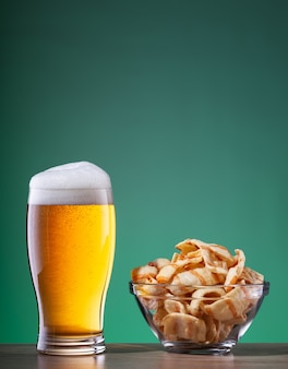 Light beer with foam in glass and snacks in transparent plate