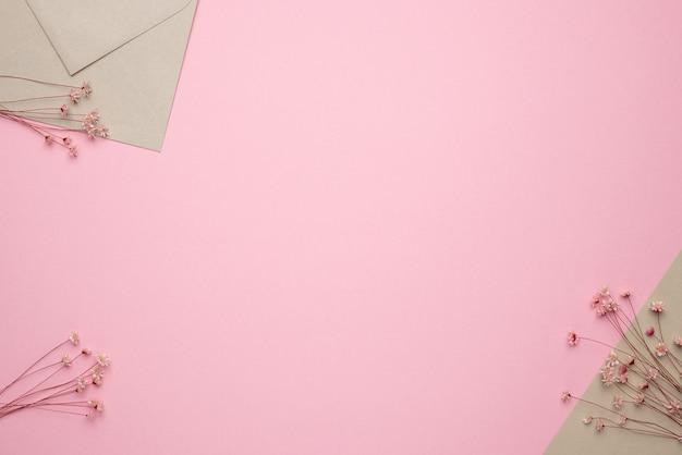 ピンクの背景にライトベージュの封筒とドライフラワーのブランション。繊細なパノラマとトレンド、最小限の乾燥したコンセプトの背景上面図