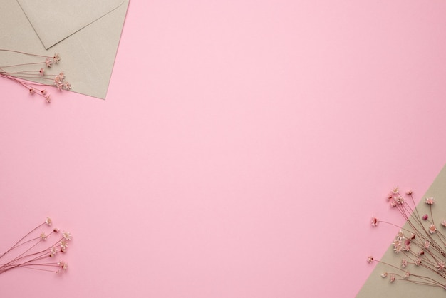 Light beige envelope ans dry flower branchon on pink background. delicate panorama and trend, minimal dried concept background top view