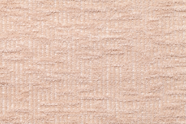 Light beige fluffy background of soft, fleecy cloth. texture of plush furry textile, closeup.