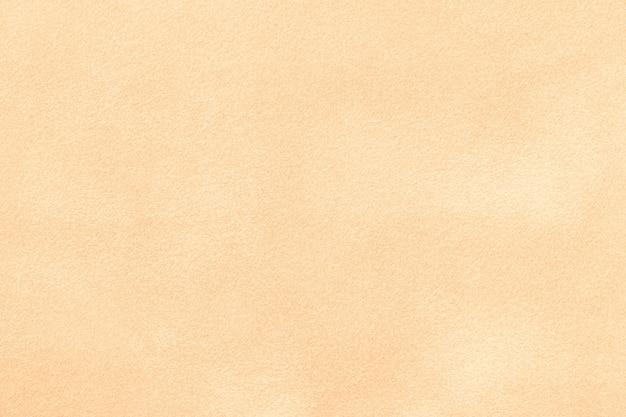 Светло-бежевый матовый фон из замшевой ткани. бархатная текстура бесшовной ткани войлока песка, макроса.