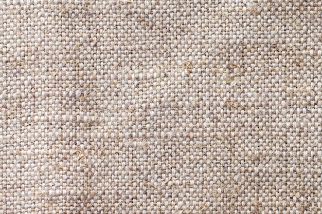 Light beige textile background closeup. structure of the fabric macro