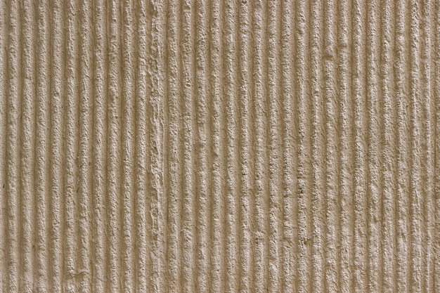 Light beige wall with a decorative plaster and vertical stripes