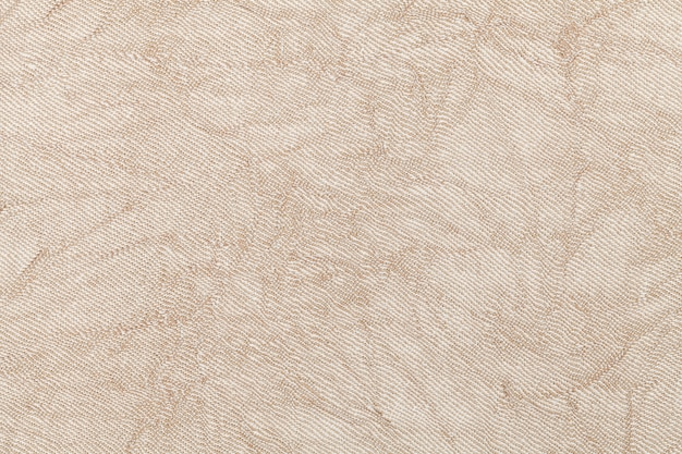 Light beige wavy background from a textile material. fabric with natural texture clousup.