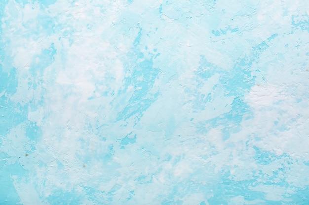 古い漆喰壁の水色の抽象的なテクスチャ。