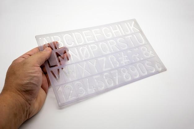 Light blue alphabet stencil lettering pvc plastic ruler template isolated on white