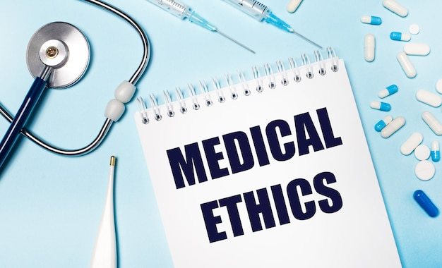 On a light blue background, an electronic thermometer, a stethoscope, white and blue pills, syringes and a notebook with the text medical ethics. medical concept