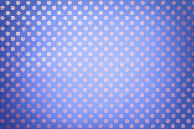 銀の水玉のクローズアップのパターンを持つ包装紙から明るい青の背景。