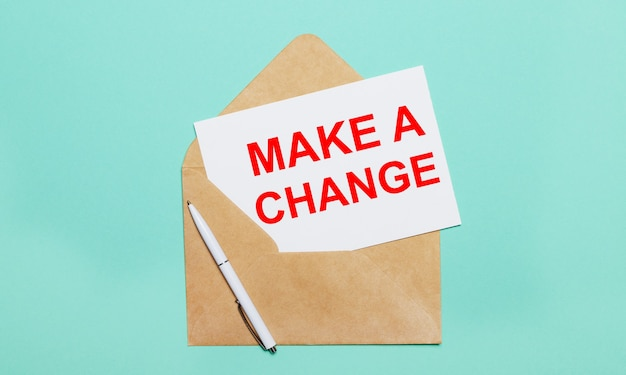 On a light blue background lies an open craft envelope, a white pen and a white sheet of paper with the text make a change