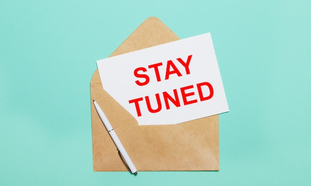 On a light blue background lies an open craft envelope, a white pen and a white sheet of paper with the text stay tuned