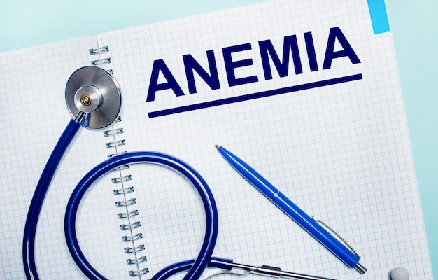 On a light blue background, an open notebook with the word anemia, a blue pen and a stethoscope