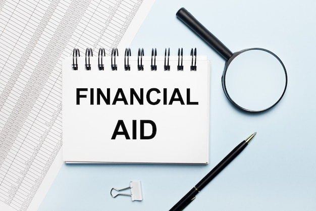 On a light blue background, reports, a magnifying glass, a pen and a notebook with the text financial aid