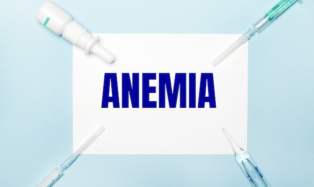 On a light blue background, syringes, a medicine bottle, an ampoule and a white sheet of paper with the text anemia. medical concept.