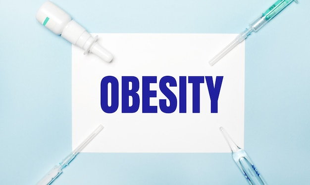 On a light blue background, syringes, a medicine bottle, an ampoule and a white sheet of paper with the text obesity. medical concept.