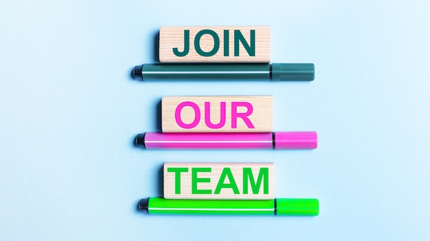 On a light blue background, there are three multi-colored felt-tip pens and wooden blocks with the join our team