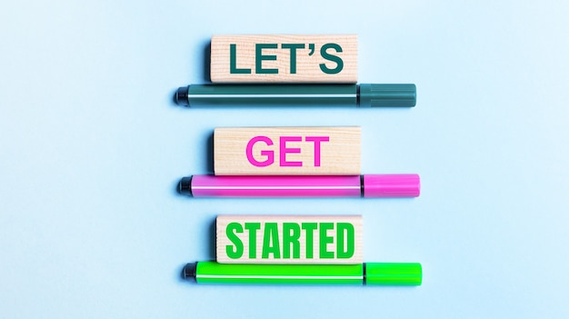 On a light blue background, there are three multi-colored felt-tip pens and wooden blocks with the let is get started text.