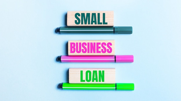 On a light blue background, there are three multi-colored felt-tip pens and wooden blocks with the small business loan.