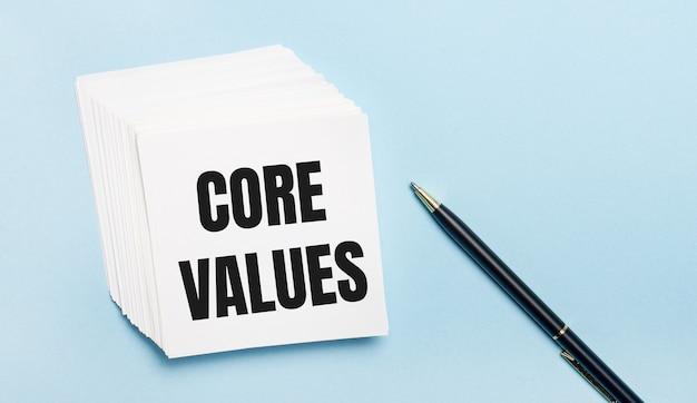 On a light blue background, there is a black pen and a stack of white note paper with the text core values