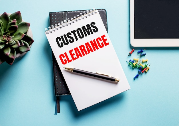 On a light blue background, there is a potted plant, a tablet and a weekly with the text customs clearance