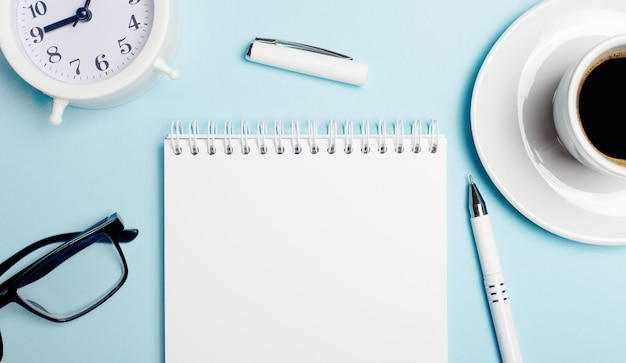 On a light blue background, there is a white alarm clock, a white cup with coffee, a white pen and a blank white notepad to insert text or illustrations. template. flat lay