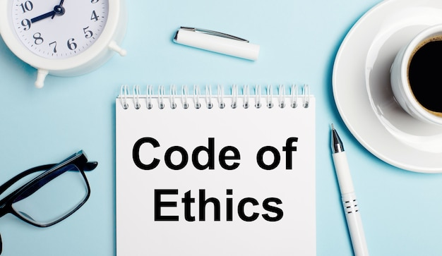On a light blue background, a white cup with coffee, a white alarm clock, a white pen and a notebook with the text code of ethics. view from above