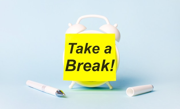 On a light blue background - a white handle and an alarm clock with a bright yellow sticker glued to it with the text take a break