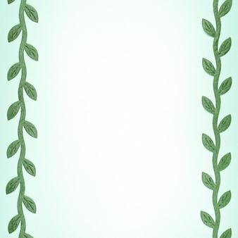 テキストと境界線上の緑の葉の枝のための場所と水色の背景。