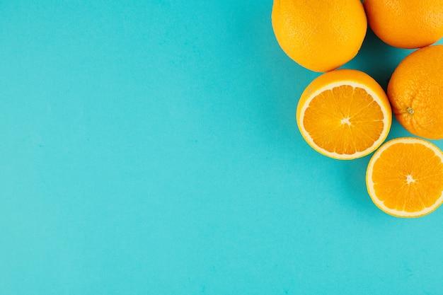 오른쪽 상단 모서리에 잘린 오렌지와 자르지 않은 오렌지가있는 밝은 파란색 배경