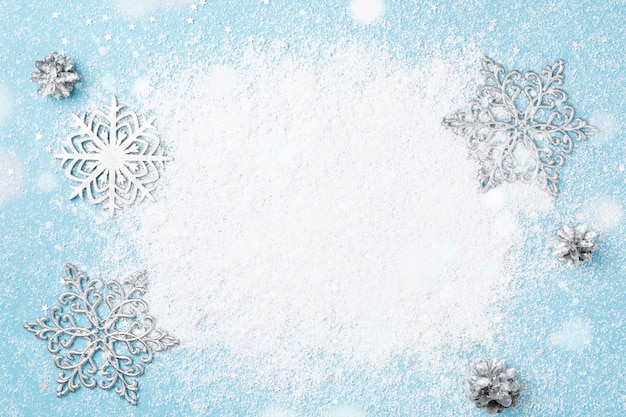 Light blue christmas and new year frame of snow and silver snowflakes.