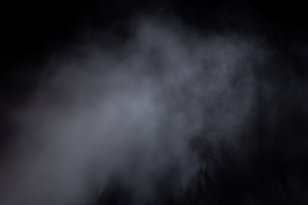 검은 배경에 고립 된 연기 증기의 밝은 파란색 구름. 가스가 폭발하고 우주에서 소용돌이친다. 추상화, 클래식 블루, 트렌디 컬러, 컬러 2020