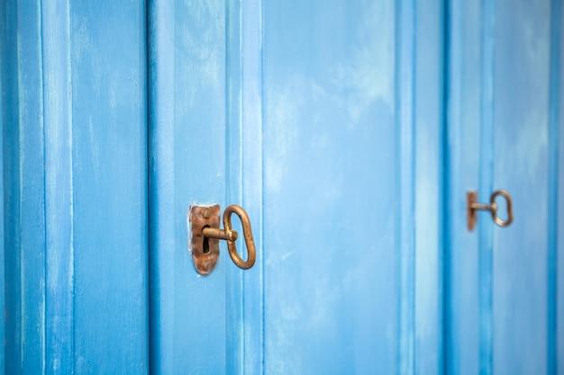녹슨 열쇠가 있는 밝은 파란색 나무 문, 빈티지 디자인 클로즈업 배경 질감, 수납장 복고풍