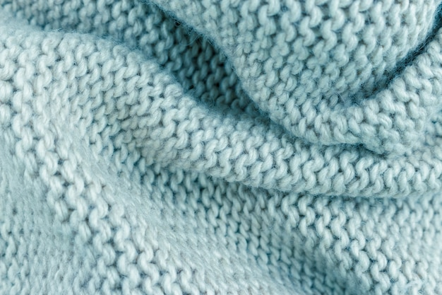 Light blue cotton knitted fabric texture background with folds. toned image