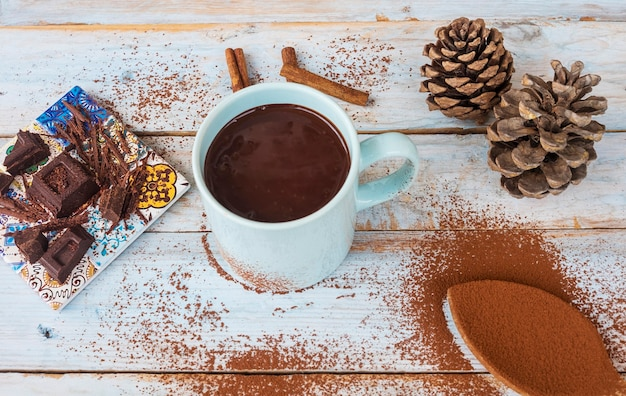 A light blue cup filled with hot thick and creamy dark chocolate rustic wooden table with spoon