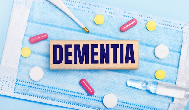 On a light blue disposable face mask there are tablets, a thermometer, an ampoule and a wooden block with the text dementia. medical concept