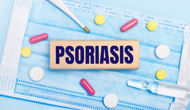 On a light blue disposable face mask there are tablets, a thermometer, an ampoule and a wooden block with the text psoriasis. medical concept
