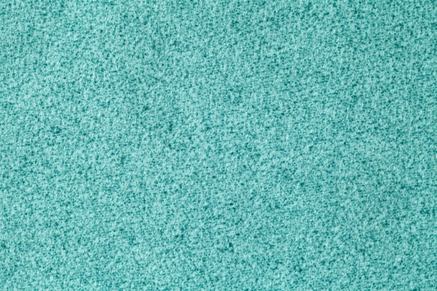 Light blue fluffy background of soft, velour fabric. texture of turquoise wool textile backdrop, closeup.