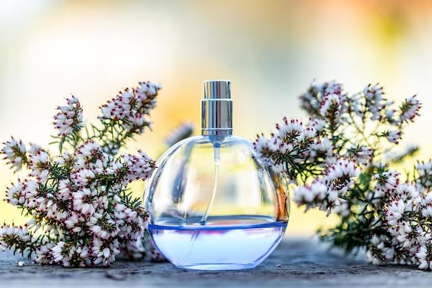 背景のボケ味の花と水色の香水瓶。香水、化粧品、フレグランスコレクション。